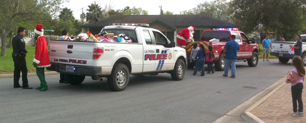 TOY DRIVE – Operation Smile is an annual event that collects unwrapped new toys for children during the holidays and then distributes them around the community before Christmas Eve. Tuesday, Dec. 23, local police officers and firemen dressed as Santa and his helpers drove around La Feria putting the gifts into the hands of children.