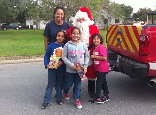 Santa poses with children while making the rounds delivering toys last Tuesday.