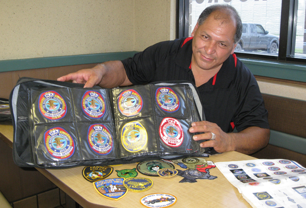 Officer Gutierrez displays just a sample of his 2,800 law enforcement patches.